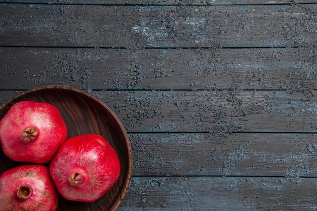 Bovenaanzicht bord met granaatappels bord met rijpe rode granaatappels aan de linkerkant van de tafel