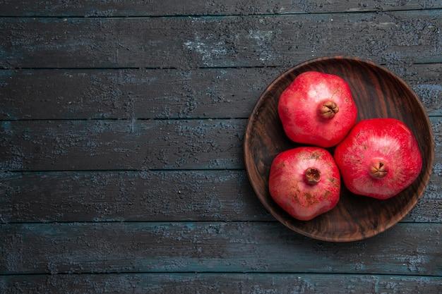 Bovenaanzicht bord met granaatappels bord met rijpe rode granaatappels aan de rechterkant van de tafel