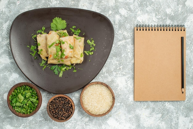 Bovenaanzicht bord van voedselbord met gevulde kool en borden met zwarte papper rijst en kruiden aan de linkerkant van de tafel naast een crème notitieboekje met potlood