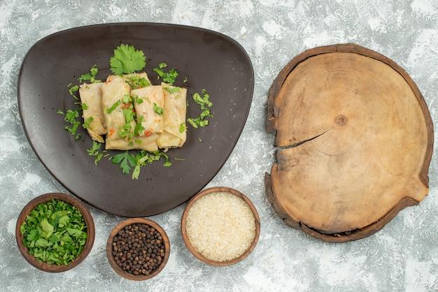 Bovenaanzicht bord van voedselbord met gevulde kool en borden met zwarte papper rijst en kruiden aan de linkerkant van de tafel naast een houten snijplank