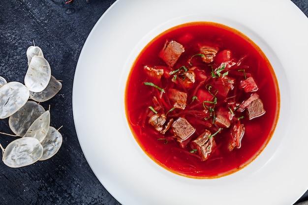 Bovenaanzicht borscht, oekraïense keuken zure soep, met vlees, aardappel, rode biet