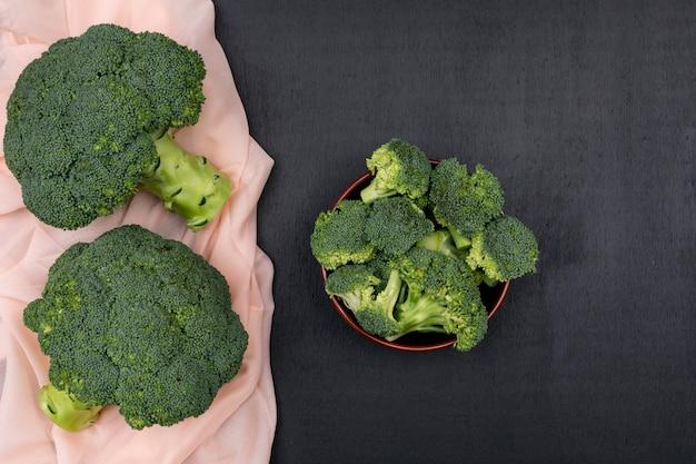 Bovenaanzicht bos van broccoli op roze doek met broccoli in keramische kom