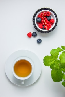 Bovenaanzicht bosbessen en frambozen in kom met aalbes, kamille thee, muntblaadjes.