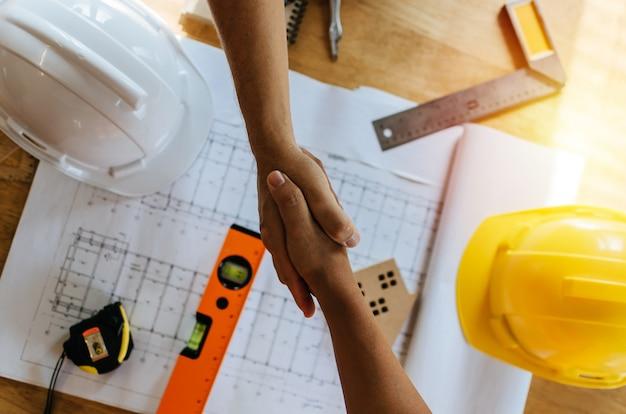 Bovenaanzicht bouwvakker team contractant handbewegingen na het beëindigen van zakelijke bijeenkomst
