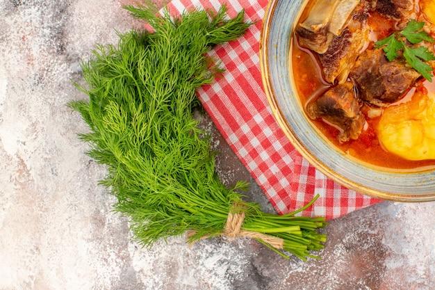 Bovenaanzicht bozbash soep keukenhanddoek een bosje dille op naakte achtergrond