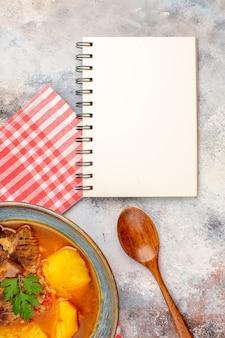 Bovenaanzicht bozbash soep keukenhanddoek een houten lepel een notitieboekje op naakte achtergrond