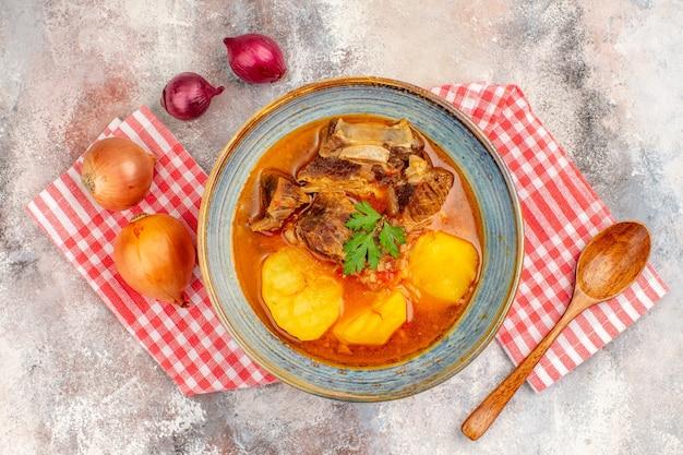 Bovenaanzicht bozbash soep keukenhanddoek een houten lepel gele en rode uien op naakte achtergrond