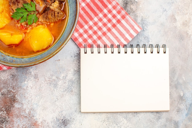 Bovenaanzicht bozbash soep keukenhanddoek een notitieboekje op naakte achtergrond