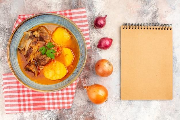 Bovenaanzicht bozbash soep keukenhanddoek gele en rode uien een notitieboekje op naakte achtergrond