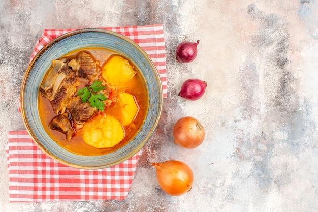 Bovenaanzicht bozbash soep keukenhanddoek gele en rode uien op naakte achtergrond