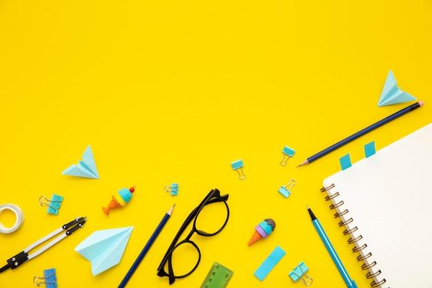 Bovenaanzicht briefpapier arrangement op gele achtergrond met kopie ruimte