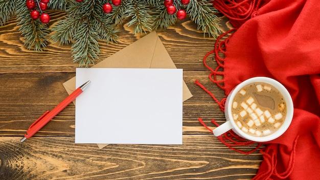 Bovenaanzicht briefpapier lege papieren en hete thee op rode sjaal