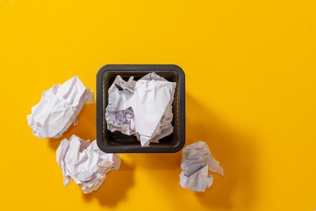Bovenaanzicht. briefpapiermand voor pennen met verfrommelde papieren ballen, conceptuele zoektocht naar ideeën, inspiratie.