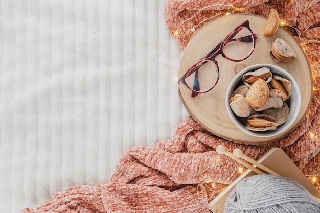 Bovenaanzicht bril op houten bord met garen en deken