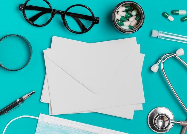 Bovenaanzicht brillen met medicijnen en enveloppen