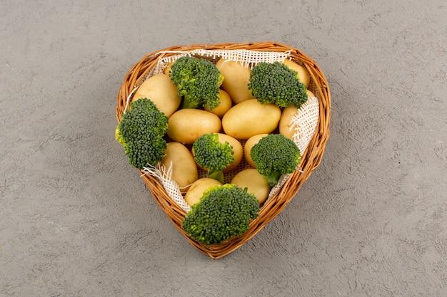 Bovenaanzicht broccoli en aardappelen rijp binnen mand op de grijze vloer