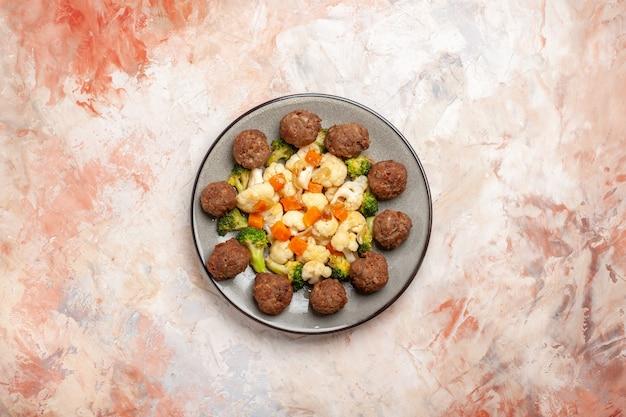 Bovenaanzicht broccoli en bloemkoolsalade en gehaktbal op plaat op naakt geïsoleerde oppervlakte vrije ruimte