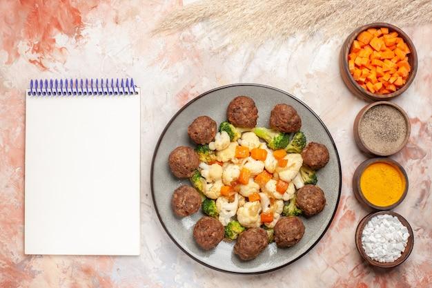 Bovenaanzicht broccoli en bloemkoolsalade en gehaktbal op witte plaat verticale rij kommen met verschillende kruiden een notitieblok op naakt oppervlak