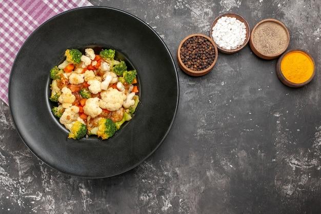 Bovenaanzicht broccoli en bloemkoolsalade in zwarte kom roze en wit geruit servet verschillende kruiden op donkere oppervlakte vrije ruimte