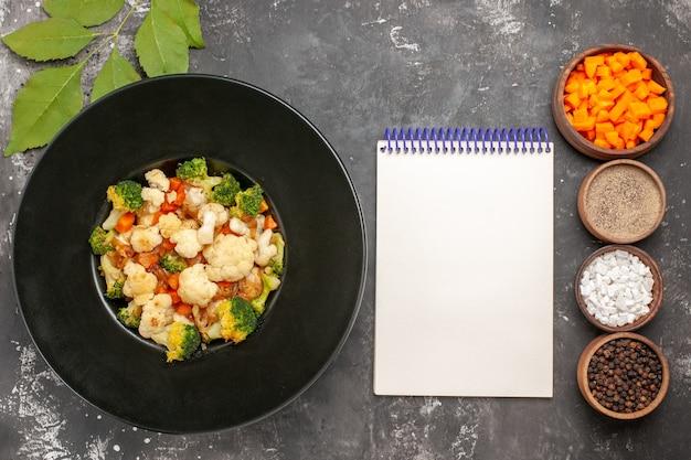 Bovenaanzicht broccoli en bloemkoolsalade in zwarte kom verschillende kruiden en wortel snijden in kommen een notitieboekje op donkere ondergrond