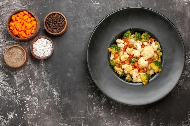 Bovenaanzicht broccoli en bloemkoolsalade in zwarte kom verschillende kruiden en wortel snijden in kommen op donkere ondergrond met kopie ruimte