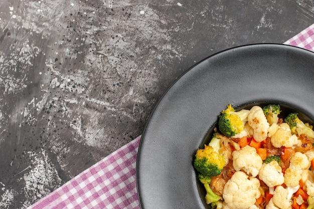 Bovenaanzicht broccoli en bloemkoolsalade op ovale plaat roze en wit geruit tafelkleed op donkere oppervlakte vrije ruimte