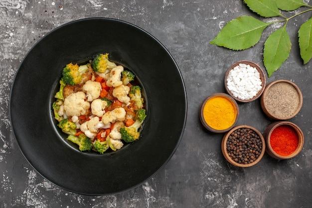 Bovenaanzicht broccoli en bloemkoolsalade op zwarte ovale plaat op dienblad kruiden in kleine kommen op donkere ondergrond
