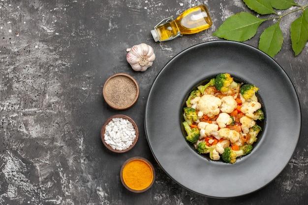 Bovenaanzicht broccoli en bloemkoolsalade op zwarte ovale plaat op dienblad kruiden olie knoflook op donkere ondergrond vrije plaats