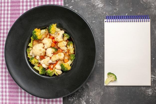 Bovenaanzicht broccoli en bloemkoolsalade op zwarte ovale plaat op dienblad roze en wit geruit tafelkleed een notitieboekje op donkere ondergrond