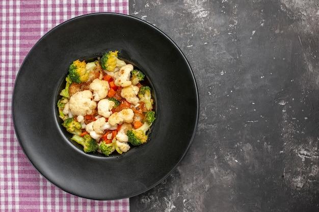 Bovenaanzicht broccoli en bloemkoolsalade op zwarte ovale plaat op dienblad roze en wit geruit tafelkleed op donkere oppervlakte vrije ruimte