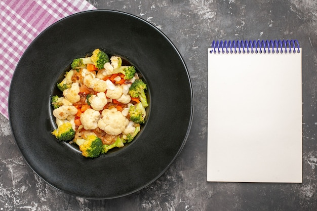Bovenaanzicht broccoli en bloemkoolsalade op zwarte ovale plaat roze en wit geruit tafelkleed een blocnote op donkere ondergrond