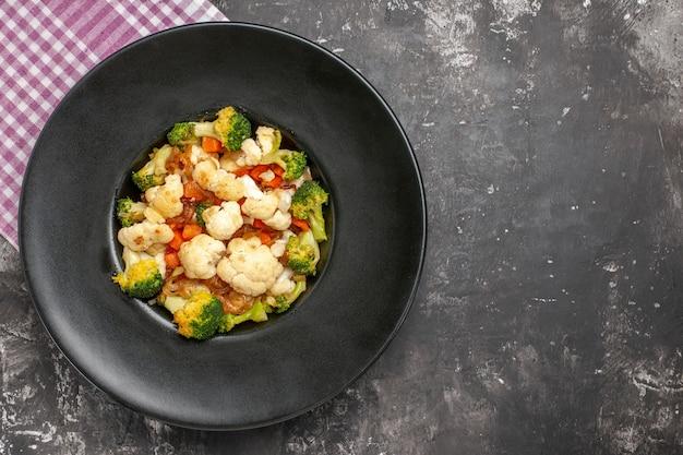 Bovenaanzicht broccoli en bloemkoolsalade op zwarte ovale plaat roze en wit geruit tafelkleed op donkere ondergrond met vrije ruimte
