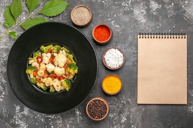 Bovenaanzicht broccoli en bloemkoolsalade op zwarte ovale plaat verschillende kruiden in kleine kommen een notitieboekje op donkere ondergrond