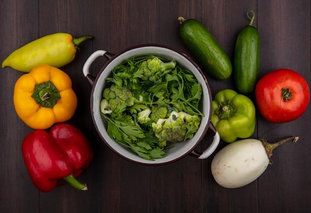 Bovenaanzicht broccoli in een pan met peterselie en komkommers en paprika's op een houten achtergrond