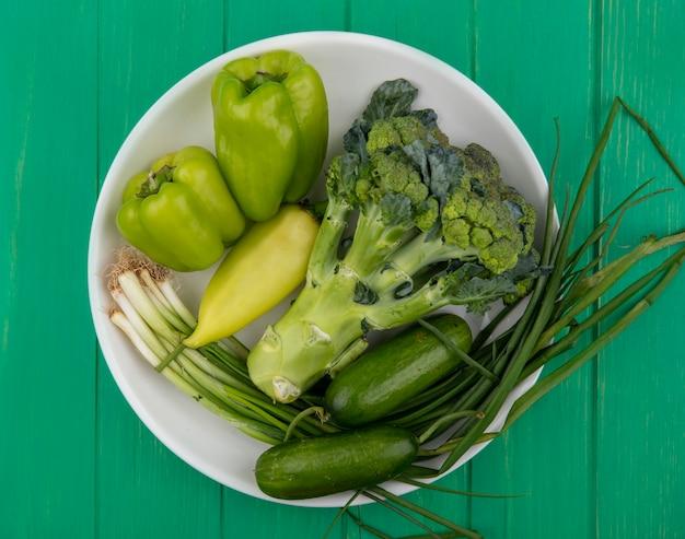 Bovenaanzicht broccoli met komkommers groene uien en paprika in een plaat op een groene achtergrond