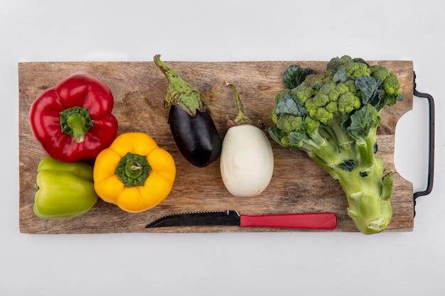 Bovenaanzicht broccoli met zwarte en witte aubergine met gekleurde paprika en een mes op een snijplank