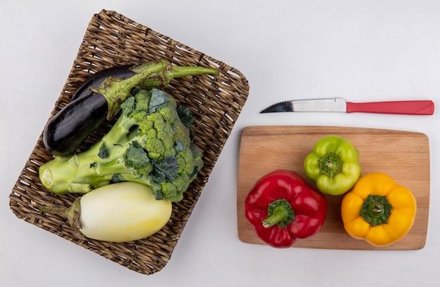 Bovenaanzicht broccoli met zwarte en witte aubergines op een stand met gekleurde paprika op een snijplank en een mes op een witte achtergrond