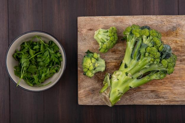 Bovenaanzicht broccoli op snijplank met peterselie in kom op houten achtergrond