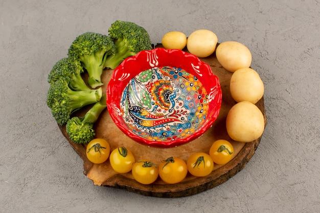 Bovenaanzicht broccoli tomaten champignons vers rijp op het bruine bureau en grijze vloer