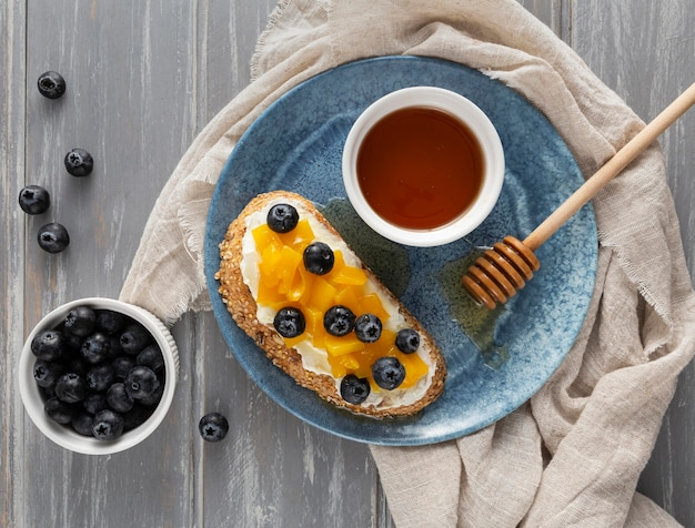 Bovenaanzicht brood met roomkaas en fruit op plaat met honing