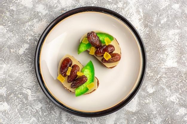 Bovenaanzicht brood toast met komkommer en gedroogde pruimen in plaat op witte muur brood toast sandwich eten ontbijt