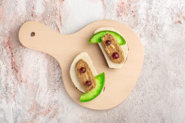Bovenaanzicht brood toast met paté en plakjes komkommer binnen plaat op witte muur vlees plantaardig voedsel toast sandwich