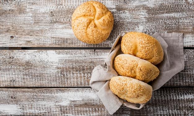 Bovenaanzicht broodjes met sesam op houten achtergrond