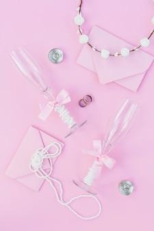 Bovenaanzicht bruiloft arrangement met champagneglazen en uitnodigingen