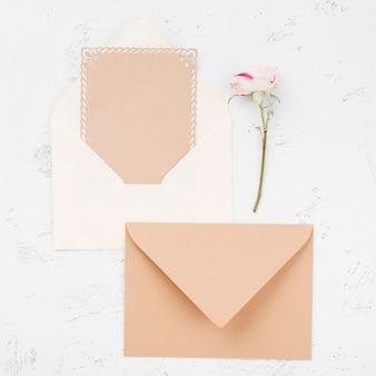 Bovenaanzicht bruiloft uitnodiging enveloppen en bloemen