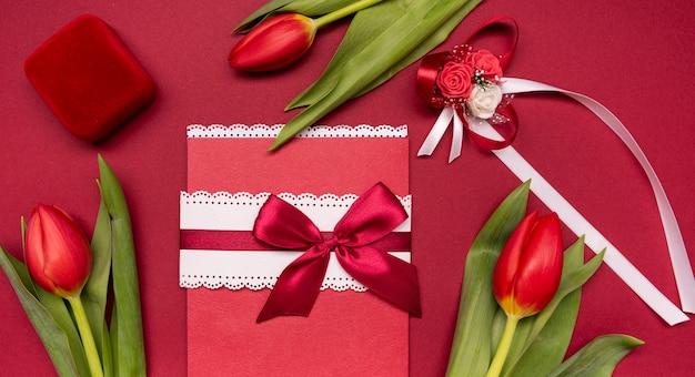 Bovenaanzicht bruiloft uitnodiging omgeven door bloemen