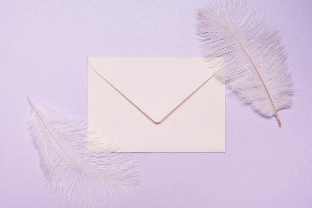Bovenaanzicht bruiloft uitnodiging omgeven door veren
