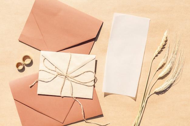 Bovenaanzicht bruiloft uitnodigingen in enveloppen met papier achtergrond