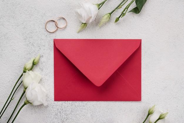 Bovenaanzicht bruiloft uitnodigingskaart met bloemen op de tafel