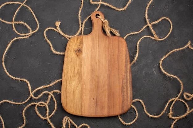 Bovenaanzicht bruin houten bureau op donkere achtergrond houten bureau touw
